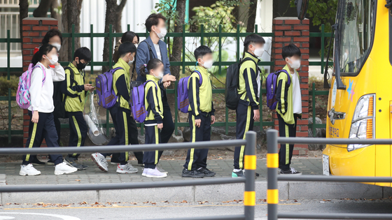 Students line up for a school bus in Nowon District, northern Seoul, Monday. Social distancing measures have been eased from Level 2 to Level 1, and Seoul education authorities said students will soon be allowed to go to school more often than before. [NEWS1]