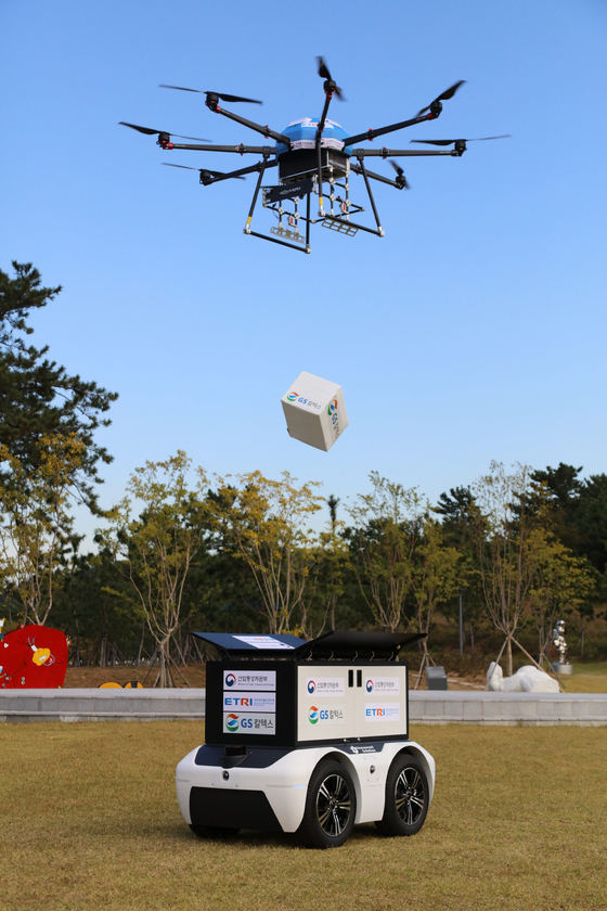 A drone passes a package to an unmanned autonomous robot in Yeosu, South Jeolla, during a demonstration Tuesday. [GS CALTEX]