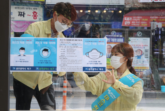 Gwangju officials tape fliers to a bus stop near Chonnam National University Tuesday informing the public about a new law on face masks. [YONHAP]