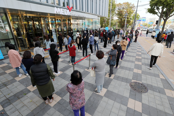 People line up for free flu vaccines for children aged 13 to 18 in front of the Korea Association of Health Promotion branch in Suwon, Gyeonggi, Tuesday. Free flu shots will be administered for the elderly starting next week. [NEWS1]
