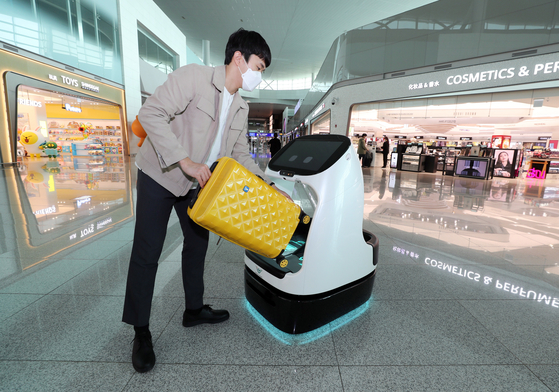 A man uses an autonomous cart at the departure gate of Incheon International Airport's Terminal 2 on Wednesday. Incheon International Airport said it is operating a trial run for the indoor autonomous vehicles, the first airport in the world to do so. [YONHAP]