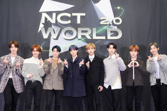 """Members of NCT (from left) Sungchan, Kun, Jeno, Taeyong, Winwin, Doyoung, Chenle and Shotaro pose for photos prior to the online press conference for """"NCT World 2.0"""" held on Wednesday afternoon. [MNET]"""