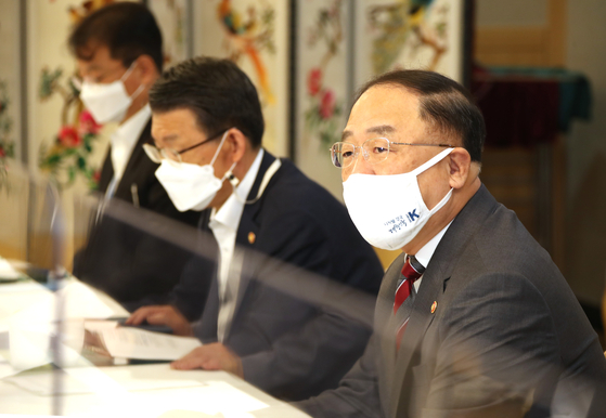 Finance Minister Hong Nam-ki, right, speeaks during the government's meeting on real estate market held at the government complex in Seoul on Wednesday. [YONHAP]