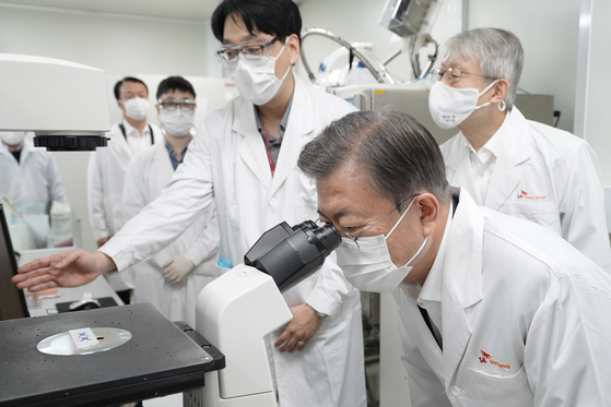 President Moon Jae-in looks into a microscope at a laboratory in SK Bioscience's research institute in Seongnam, Gyeonggi on Thursday. [YONHAP]