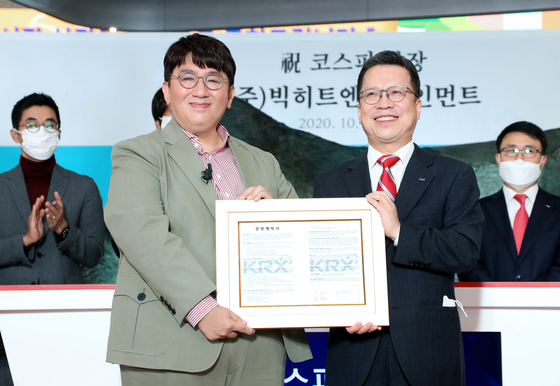 Big Hit Entertainment Chairman Bang Si-hyuk, left, and Korea Exchange CEO and Chairman Jung Ji-won pose for a photo holding a memorial tablet celebrating the company's public listing on Oct. 15 at the exchange's headquarters in Yeouido, western Seoul. [BIG HIT ENTERTAINMENT]