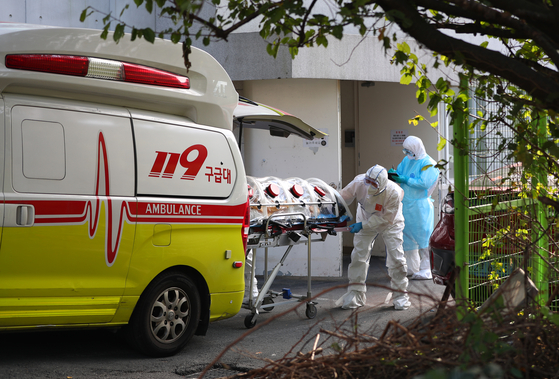 A coronavirus patient at a hospital for senior citizens in Busan gets transferred to a different hospital Wednesday after developing severe symptoms. At least 53 Covid-19 cases have been traced to the Busan hospital, making it the largest cluster the city has seen. [YONHAP]