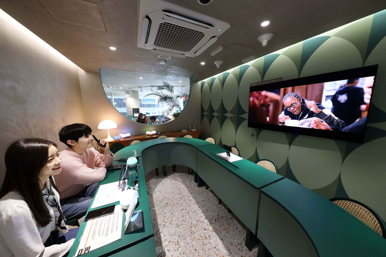 Models watch the screen at a meeting room operated through Google's artificial intelligence (AI) speaker in a cultural complex run by mobile carrier LG U+ in Gangnam District, southern Seoul. Named Daily_Teum, the six-story building houses a cafe, independent bookstore, photo studio and meeting room. The carrier explained that it displayed a wide range of devices and smartphones offered by LG U+ in each section to develop the place into a unique experience zone. [LG U+]