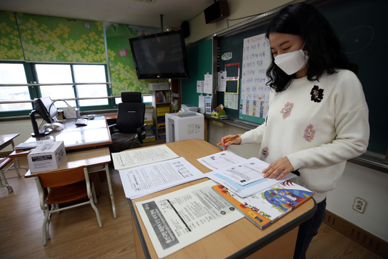 A teacher prepares for class at Itaewon Elementary School on Friday. Starting Monday, kindergartens, elementary and middle schools throughout the country, which have been allowing only one-third of the student body to be present in school at a time, will allow up to two-thirds of students to return.  [YONHAP]
