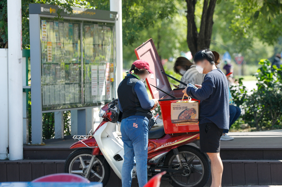A delivery rider delivers food to a customer in Yeouido, western Seoul, in September. [NEWS1]