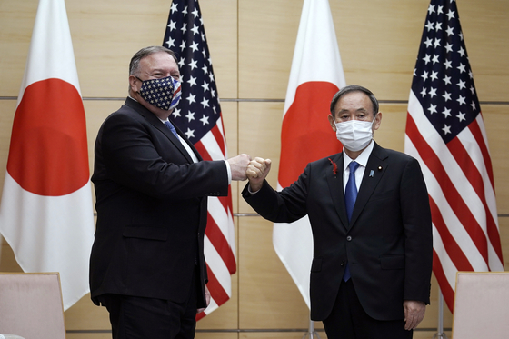 Japan's Prime Minister Yoshihide Suga, right, and U.S. Secretary of State Mike Pompeo, left, greet each other prior to their meeting at the prime minister's office on Oct. 6 in Tokyo. [AP/YONHAP]