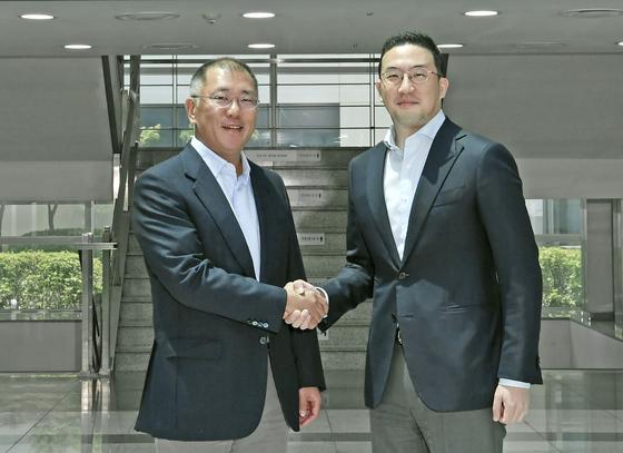 Hyundai Motor Group Chairman Euisun Chung, left, shakes hands with LG Group Chairman Koo Kwang-mo at LG Chem's battery factory in Ochang, North Chungcheong, in June. [HYUNDAI MOTOR GROUP]