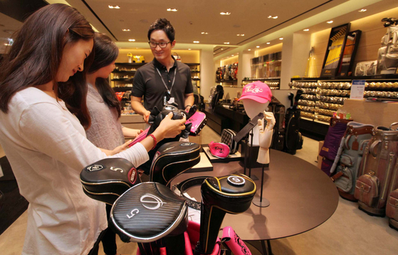 A female customer looks at golf equipment at the golf department of a Shinsegae Department Store. [SHINSEGAE DEPARTMENT STORE]