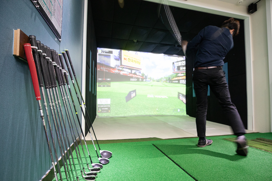 A golfer practices at a screen golf practice center in Seoul on Oct. 13. [YONHAP]