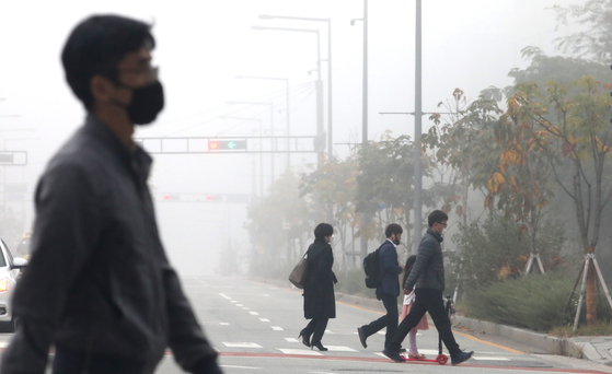 """Commuters walk through smog on Tuesday as the comprehensive air quality index reached """"bad"""" levels in Sejong. [NEWS1]"""