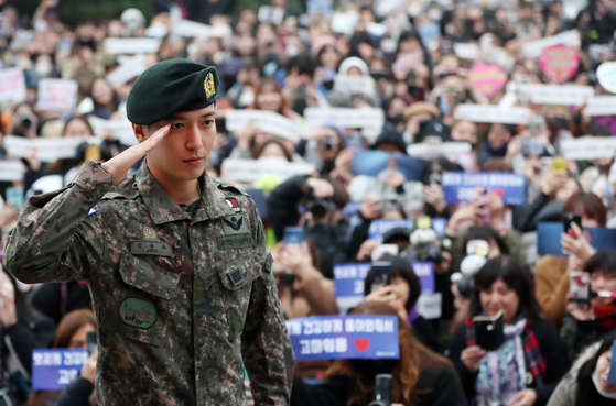 Singer Jung Yong-hwa salutes as fans await to welcome him back on Nov. 3, 2019, after he finished his two-year mandatory military service. [YONHAP]