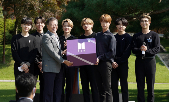 President Moon Jae-in receiving a present from boy band BTS on Sept. 19, after inviting the band to the first Youth Day ceremony held at the Blue House, central Seoul. [YONHAP]