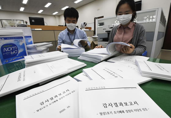 National Assembly workers look at copies of a report submitted by the Board of Audit and Inspection on the government's decision to shut down the Wolsong I nuclear reactor. [YONHAP]