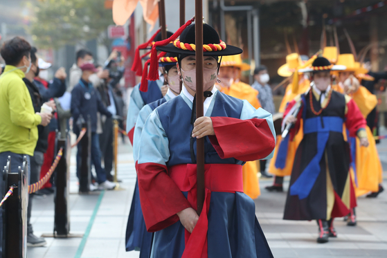 At the main gate of Deoksu Palace in central Seoul on Tuesday, actors resume the daily changing of the guard ceremony, which has been suspended since Feb. 1 because of the Covid-19 outbreak. [YONHAP]