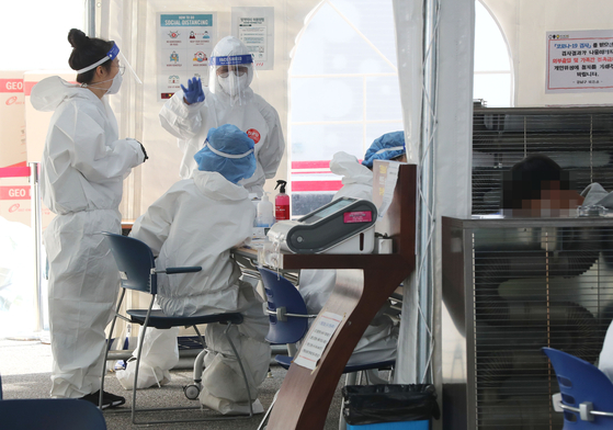 Medical staff in full quarantine gear are seen at a testing center in Gangnam District, southern Seoul, on Tuesday. [YONHAP]