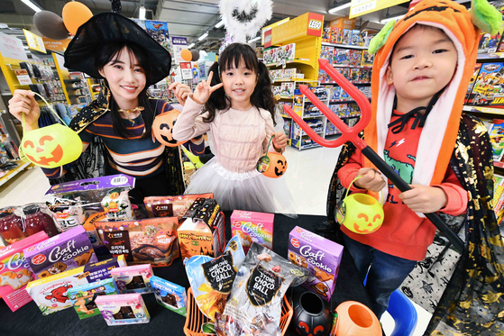 Models pose with Halloween-related merchandise at Homeplus' Gangseo branch in western Seoul on Wednesday. The retailer said it is holding a special event celebrating the spooky celebration until the end of this month including selling 20,000 bottles of a limited Halloween edition of Seoul Milk's ABC Juice. [HOMEPLUS]