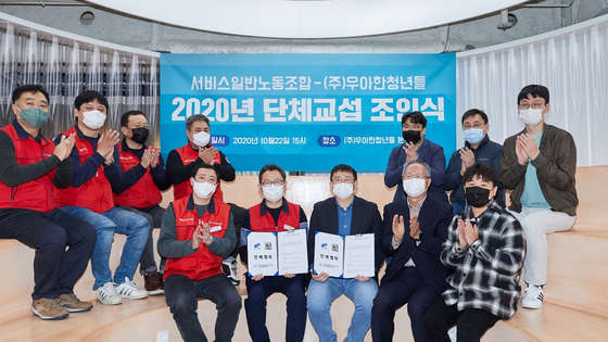 Woowahan Youths CEO Kim Byoung-woo, third from left in the front row, and representatives from the Korean Federation of Service Worker's Union pose for a photo after signing a collective bargaining agreement in Seocho District, southern Seoul on Thursday. [WOOWAHAN YOUTHS]