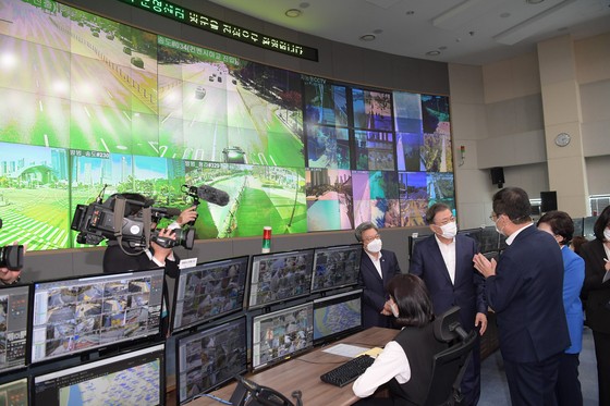 President Moon Jae-in, center, receives a report on managing smart cities at Songdo's smart city management center in Incheon on Thursday. It was Moon's first tour on the regional-balanced New Deal. [JOINT PRESS CORPS]