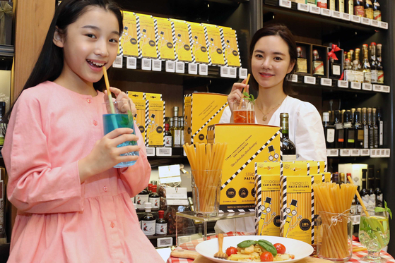 Models pose with spaghetti noodles that can double as straws at Shinsegae Department Store's main branch in Seoul on Thursday. The pasta noodles were created by British company Stroodles. [SHINSEGAE DEPARTMENT STORE]