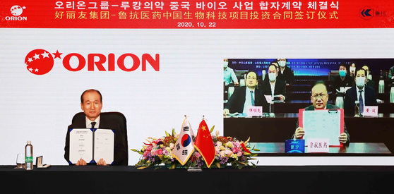 Orion Holdings CEO Hur Inn-chul, left, and Shandong Lukang Pharmaceutical President Peng Xin during a ceremony celebrating the signing of the two companies' plan to establish a joint venture. [ORION HOLDINGS]