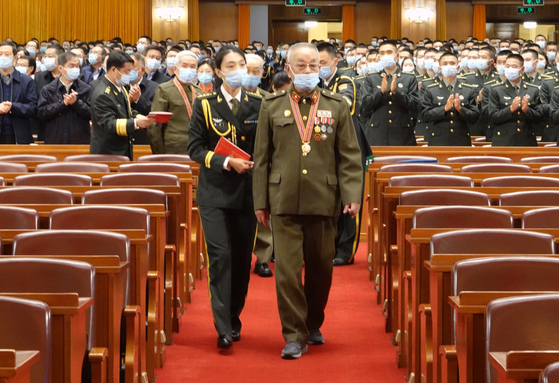 A Chinese People's Volunteers veteran enters the venue of the meeting marking the 70th anniversary of the CPV entering North Korea to participate in the Korean War at the Great Hall of the People in Beijing on Friday.  [XINHUA]