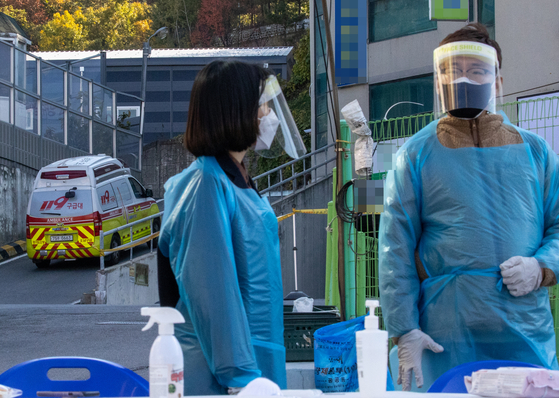 An ambulance enters a building linked to a Covid-19 outbreak in Namyangju, Gyeonggi, on Friday. [YONHAP]