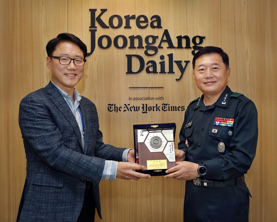 Lt. Gen. Chung Jin-kyung, right, superintendent of the Korea Military Academy, awards a plaque of appreciation to Ryu Kwon-ha, left, CEO of the Korea JoongAng Daily, to recognize his contribution to the education of cadets, at the paper's office in Sangam-dong, western Seoul, on Monday.  [PARK SANG-MOON]