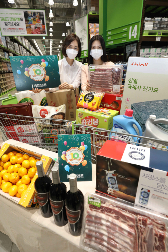 Models pose behind items on sale to celebrate the 10th anniversary of Emart's big-box warehouse chain, Emart Traders, on Monday at the store's Nowon branch in northern Seoul. Items will be available at up to 50 percent off until Nov. 1. [EMART]