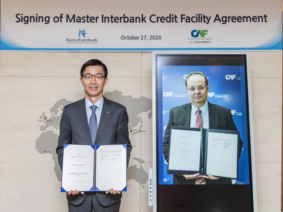 Bang Moon-kyu, chairman and president of the Export-Import Bank of Korea, and Luis Carranza, executive president and CEO of the Development Bank of Latin America, hold up the agreement signed by the two banks, in their respective countries, Tuesday. [THE EXPORT-IMPORT BANK OF KOREA]