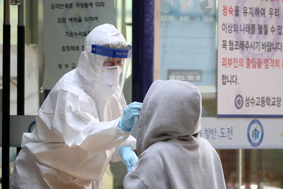 A student gets tested for coronavirus at a makeshift testing center at Seongsu High School in Seongdong District, eastern Seoul, Tuesday, after a high school senior tested positive. [NEWS1]