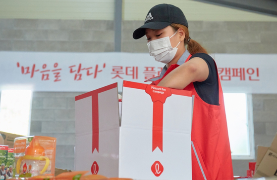 A woman packs a Lotte Pleasure Box containing various food and baby products. [LOTTE]