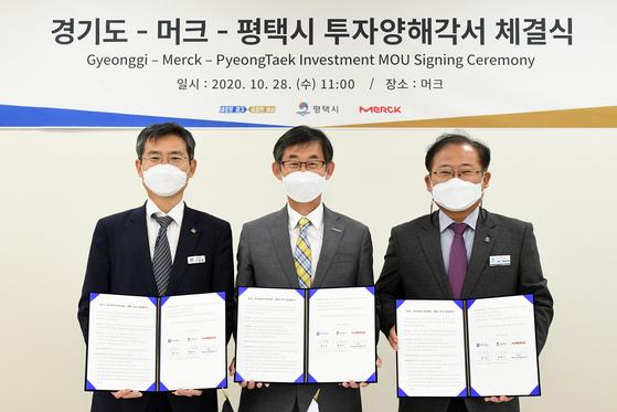 From left, Lee Yong-chul, Gyeonggi Province vice governor; Kim Woo-kyu, managing director of Merck Korea and Lee Jong-ho, Pyeongtaek City vice mayor, pose after signing an agreement on Wednesday. [MERCK KOREA]