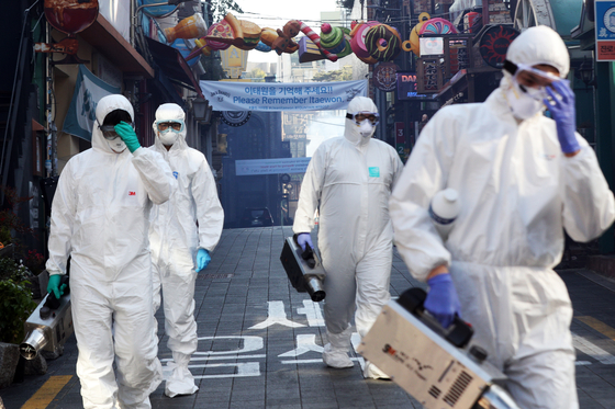 Officials from the Yongsan District Office disinfect streets in Itaewon, central Seoul, on Thursday ahead of Halloween in efforts to prevent new infections of Covid-19. [NEWS1]