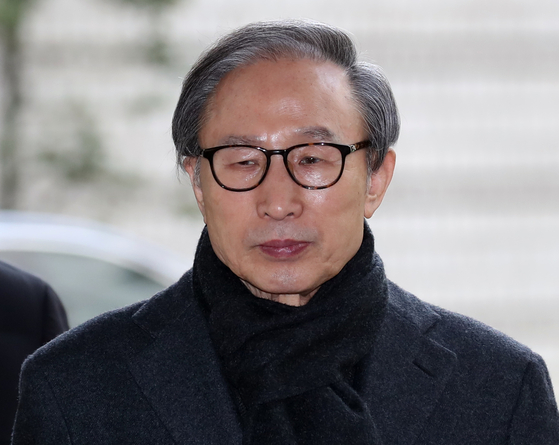 In this file photo, former President Lee Myung-bak enters the Seoul High Court on Feb. 19 to attend a sentencing hearing. On Thursday, the Supreme Court upheld the high court's rulings and sentence against Lee. [YONHAP]