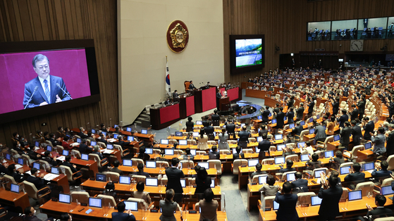 President Moon Jae-in receives a standing ovation from ruling Democratic Party lawmakers Wednesday after he announced a pledge to achieve net-zero carbon emissions by 2050. [YONHAP]