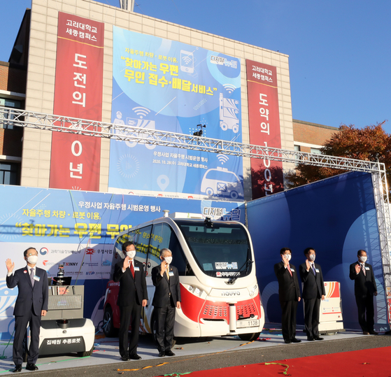 Participants in Korea Post's demonstration event on Wednesday are photographed at Korea University's Sejong Campus, where the event took place. The event showcased new high-tech postal service devices, such as an autonomous post office and an assistant delivery robot. [NEWS 1]