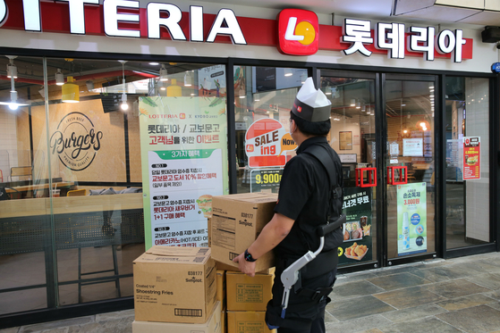 A Lotteria employee carries heavy boxes wearing a wearable robot that lightens the weight of the boxes. [LOTTE GRS]