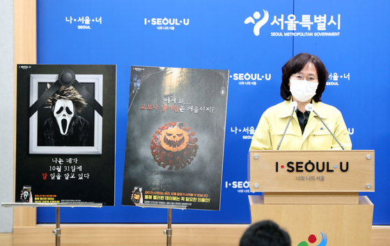 Park Yoo-mi, the Seoul city government's director of public health, on Wednesday shows posters made by the city to discourage potential revelers from celebrating Halloween over the weekend. [YONHAP]