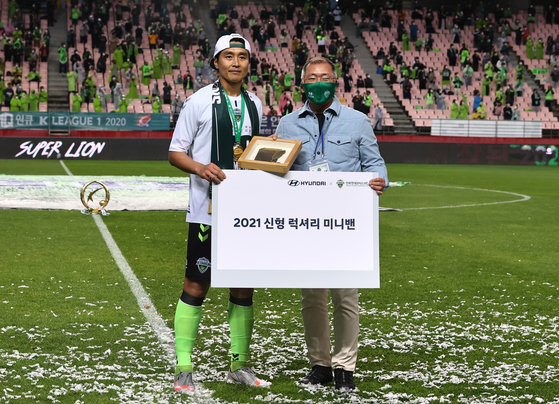 Lee Dong-gook, left, of Jeonbuk Hyundai Motors poses for a photo after receiving an appreciation plaque from Hyundai Motors Chairman Euisun Chung, right, during his retirement ceremony in Jeonju on Sunday. [YONHAP]