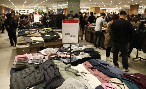 Shoppers browse discounted clothes at a department store in Seoul on Sunday as this year's Korea Sale Festa began. The nationwide shopping promotion that takes place at 1,633 department stores, supermarkets and convenience stores will run through Nov. 15 and offer a wide range of discounts. [YONHAP]