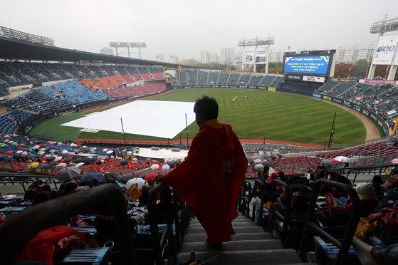 Fans wait for Game 1 of the Wildcard Series between the LG Twins and the Kiwoom Heroes to start amid pouring rain at Jamsil Baseball Stadium in southern Seoul on Nov. 1. The game was ultimately canceled and rescheduled for Monday at 6:30 p.m. [YONHAP]