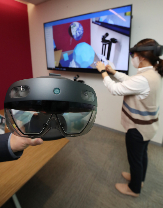 A participant tries on Microsoft's HoloLens 2 at Microsoft Korea's office in Jongno District, central Seoul, on Monday during an online press conference for the product's release in Korea. The price of the mixed reality (MR) device, which is a wearable holographic computer suited to corporations, is estimated to be between 5.5 million won ($4,845) and 5.8 million won. [YONHAP]