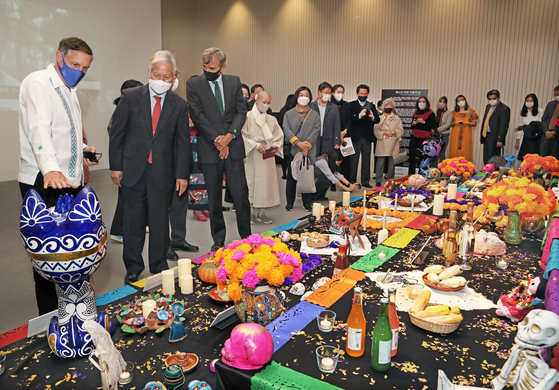 """From left, Bruno Figueroa, ambassador of Mexico to Korea, Bae Ki-dong, director of the National Museum of Korea, Juan Ignacio Morro Villacian, ambassador of Spain to Korea and other guests view """"Mexico's Day of the Dead Offering"""" exhibition at the museum in central Seoul on Oct. 30. [PARK SANG-MOON]"""