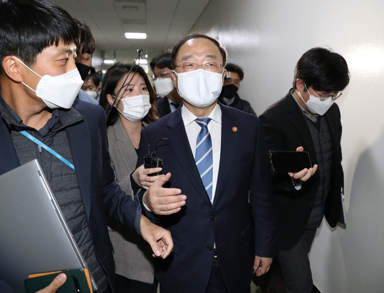 Finance Minister Hong Nam-ki is surrounded by reporters after exiting a meeting with lawmakers at the National Assembly on Nov. 3 in Seoul. [YONHAP]
