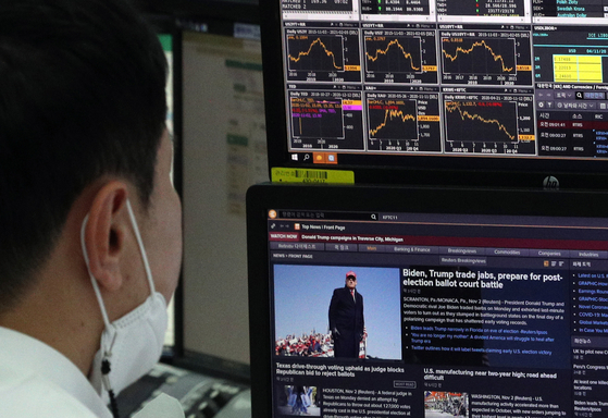 A stockbroker reads news about the U.S. presidential election, Tuesday, in the trading room of Hana Bank, Jung District, central Seoul. Amid anticipation, the Kospi index rose 43.15 points, or 1.88 percent, to 2,343.31. Voting is Tuesday across the United States. [NEWS1]