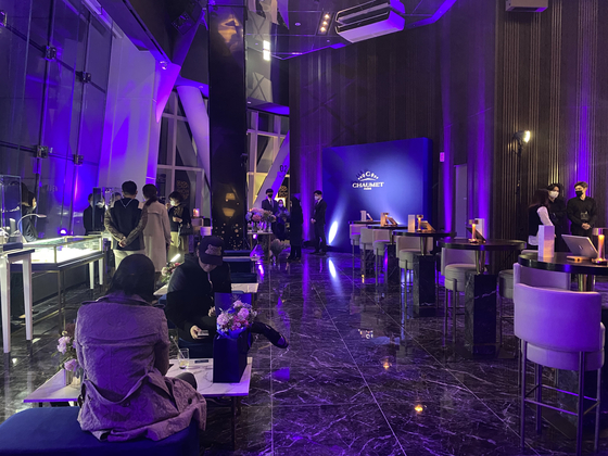 """Customers sip cocktails and examine jewelry at Lotte Department Store's 'Young & Rich D-Show"""" event held at the top floor lounge of Lotte Tower, the highest skyscraper in Korea. [LOTTE DEPARTMENT STORE]"""